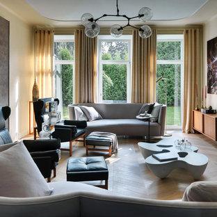 На фото: парадные гостиные комнаты в стиле ретро с бежевыми стенами, светлым паркетным полом, камином и бежевым полом