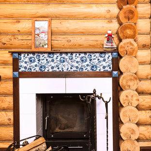 モスクワの小さいカントリー風おしゃれな独立型リビング (標準型暖炉、タイルの暖炉まわり、茶色い壁、セラミックタイルの床、壁掛け型テレビ、青い床) の写真