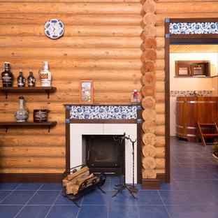 Foto di un piccolo soggiorno country chiuso con pareti marroni, pavimento con piastrelle in ceramica, camino classico, cornice del camino piastrellata, TV a parete e pavimento blu