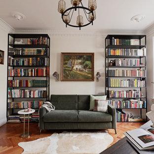 Inredning av ett modernt vardagsrum, med ett bibliotek, vita väggar och mellanmörkt trägolv