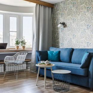 На фото: парадные, открытые гостиные комнаты в скандинавском стиле с серыми стенами, паркетным полом среднего тона и коричневым полом
