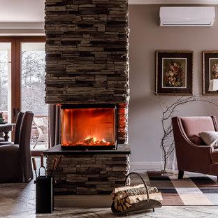 На фото: парадные гостиные комнаты в стиле современная классика с коричневыми стенами, ковровым покрытием, фасадом камина из камня, серым полом и двусторонним камином