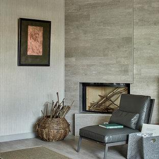 Стильный дизайн: гостиная комната в современном стиле с серыми стенами, угловым камином и серым полом - последний тренд