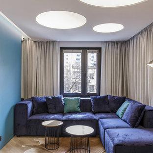 Удачное сочетание для дизайна помещения: гостиная комната в современном стиле с синими стенами, паркетным полом среднего тона и коричневым полом - самое интересное для вас
