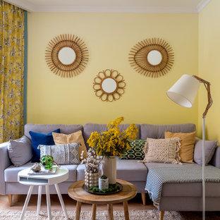 Aménagement d'un salon bord de mer de taille moyenne avec un mur jaune, aucune cheminée et un sol en bois clair.
