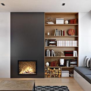 Mittelgroßes Nordisches Wohnzimmer mit weißer Wandfarbe, braunem Holzboden, Gaskamin, Kaminumrandung aus Metall und verstecktem TV in Valencia
