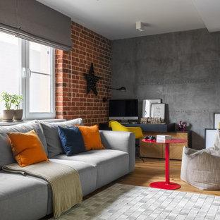 Новые идеи обустройства дома: открытая гостиная комната в стиле лофт с серыми стенами и паркетным полом среднего тона