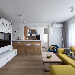Неиссякаемый источник вдохновения для домашнего уюта: открытая гостиная комната в современном стиле с белыми стенами, паркетным полом среднего тона, телевизором на стене и коричневым полом