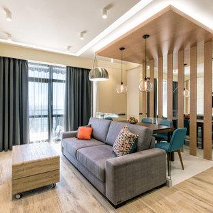 Неиссякаемый источник вдохновения для домашнего уюта: парадная, открытая гостиная комната в современном стиле с белыми стенами, телевизором на стене, паркетным полом среднего тона и коричневым полом