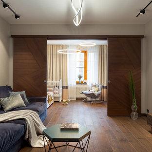 Новые идеи обустройства дома: большая гостиная комната в современном стиле с бежевыми стенами, паркетным полом среднего тона, телевизором на стене и коричневым полом