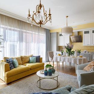 Новые идеи обустройства дома: большая открытая гостиная комната в стиле современная классика с желтыми стенами, паркетным полом среднего тона и коричневым полом