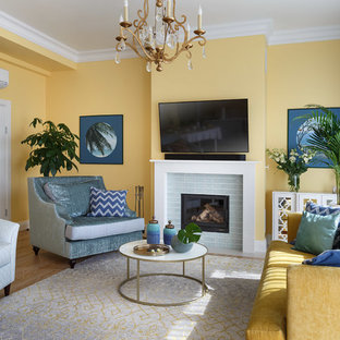 Photo of a large traditional formal living room in Saint Petersburg with yellow walls, medium hardwood flooring, a standard fireplace, a wall mounted tv, brown floors and a tiled fireplace surround.