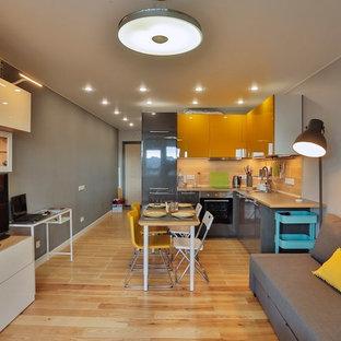 На фото: маленькая открытая гостиная комната в современном стиле с серыми стенами, паркетным полом среднего тона, отдельно стоящим ТВ и коричневым полом с