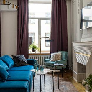 На фото: гостиная комната среднего размера в стиле современная классика с серыми стенами, паркетным полом среднего тона, стандартным камином, телевизором на стене, коричневым полом и панелями на стенах