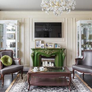 Пример оригинального дизайна: маленькая изолированная, парадная гостиная комната в стиле современная классика с бежевыми стенами, темным паркетным полом, фасадом камина из дерева, телевизором на стене и коричневым полом