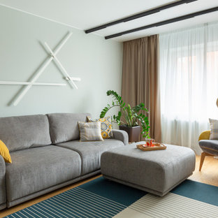 На фото: открытая гостиная комната среднего размера в современном стиле с зелеными стенами, светлым паркетным полом и бежевым полом с