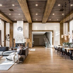Foto de salón con rincón musical tipo loft, contemporáneo, extra grande, con paredes blancas, suelo de madera en tonos medios, chimenea tradicional, marco de chimenea de piedra, televisor colgado en la pared y suelo marrón