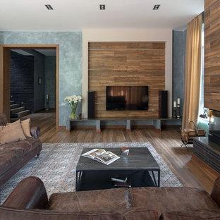 На фото: большая открытая гостиная комната в современном стиле с серыми стенами, полом из керамогранита, фасадом камина из плитки, телевизором на стене, стандартным камином и коричневым полом с