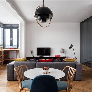 Неиссякаемый источник вдохновения для домашнего уюта: маленькая открытая гостиная комната в современном стиле с белыми стенами, паркетным полом среднего тона, отдельно стоящим ТВ и коричневым полом без камина