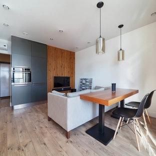 Пример оригинального дизайна интерьера: открытая гостиная комната в современном стиле с белыми стенами, светлым паркетным полом, телевизором на стене и бежевым полом