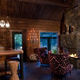 На фото: гостиная комната в стиле рустика с камином, фасадом камина из камня, домашним баром, коричневыми стенами и коричневым полом без ТВ с