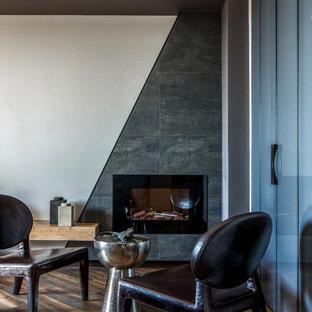 На фото: доступные гостиные комнаты среднего размера в современном стиле с серыми стенами, полом из ламината, фасадом камина из плитки, коричневым полом и камином