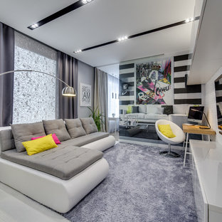 Выдающиеся фото от архитекторов и дизайнеров интерьера: изолированная гостиная комната в современном стиле с разноцветными стенами, светлым паркетным полом и телевизором на стене