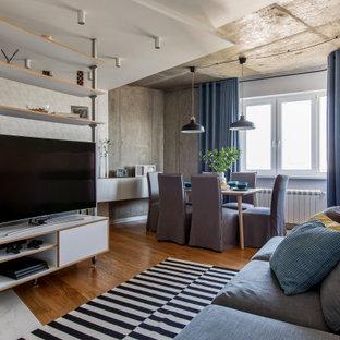 Свежая идея для дизайна: открытая гостиная комната в современном стиле с серыми стенами, паркетным полом среднего тона, отдельно стоящим ТВ и коричневым полом - отличное фото интерьера
