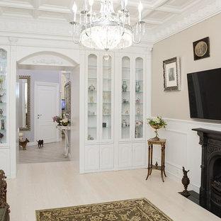 Идея дизайна: гостиная комната в классическом стиле с бежевыми стенами, светлым паркетным полом, телевизором на стене и бежевым полом