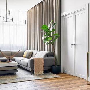 На фото: гостиная комната в современном стиле с белыми стенами и коричневым полом