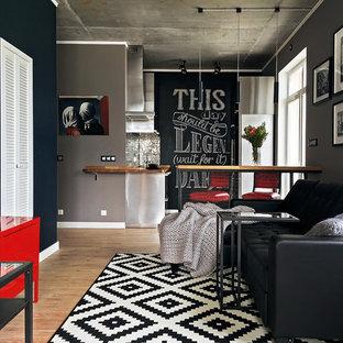 На фото: открытые гостиные комнаты среднего размера в современном стиле с полом из ламината, серыми стенами и коричневым полом