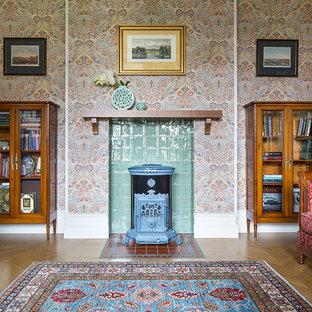 モスクワの中サイズのエクレクティックスタイルのおしゃれなリビング (フォーマル、マルチカラーの壁、淡色無垢フローリング、薪ストーブ、タイルの暖炉まわり) の写真