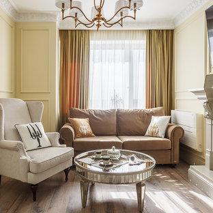 Пример оригинального дизайна: парадная гостиная комната в классическом стиле с желтыми стенами, паркетным полом среднего тона, телевизором на стене, стандартным камином и коричневым полом