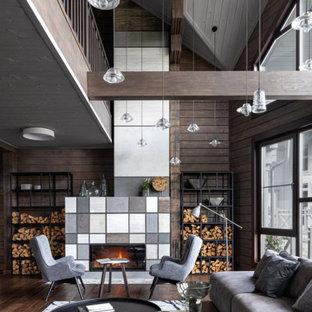 Неиссякаемый источник вдохновения для домашнего уюта: большая парадная, двухуровневая гостиная комната в современном стиле с коричневыми стенами, паркетным полом среднего тона, стандартным камином, фасадом камина из плитки и коричневым полом