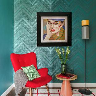 Modern inredning av ett litet separat vardagsrum, med gröna väggar, mörkt trägolv, en väggmonterad TV och brunt golv