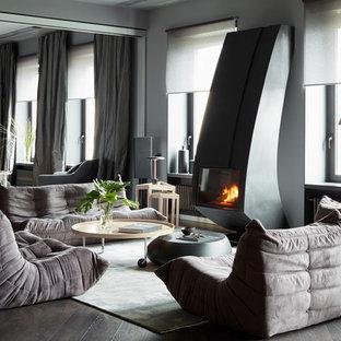 Пример оригинального дизайна: гостиная комната в современном стиле с серыми стенами, темным паркетным полом, стандартным камином и черным полом