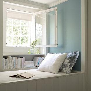 На фото: гостиные комнаты в морском стиле с библиотекой и синими стенами