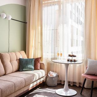 На фото: открытая гостиная комната среднего размера в скандинавском стиле с с книжными шкафами и полками, зелеными стенами, полом из керамогранита и коричневым полом