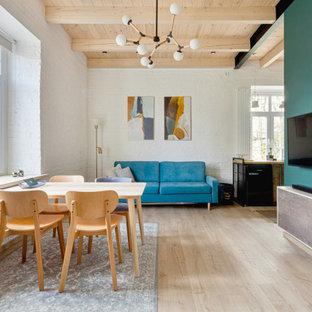 Неиссякаемый источник вдохновения для домашнего уюта: открытая гостиная комната в стиле лофт с синими стенами, светлым паркетным полом, телевизором на стене, бежевым полом, балками на потолке, деревянным потолком и кирпичными стенами