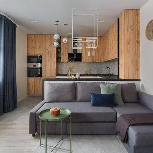 Modelo de salón con barra de bar abierto, moderno, de tamaño medio, con paredes beige, suelo laminado, chimenea tradicional, marco de chimenea de piedra, televisor colgado en la pared y suelo beige
