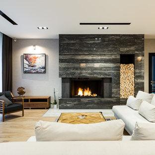 Неиссякаемый источник вдохновения для домашнего уюта: большая открытая гостиная комната в современном стиле с серыми стенами, паркетным полом среднего тона, горизонтальным камином, фасадом камина из камня, отдельно стоящим ТВ и бежевым полом