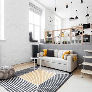 Cette photo montre un salon mansardé ou avec mezzanine tendance de taille moyenne avec un mur blanc, un sol en contreplaqué et un sol beige.