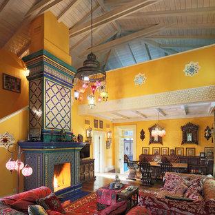Неиссякаемый источник вдохновения для домашнего уюта: огромная открытая гостиная комната в восточном стиле с желтыми стенами, стандартным камином, фасадом камина из плитки и отдельно стоящим ТВ