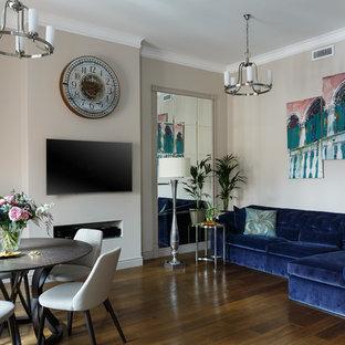 Идея дизайна: большая открытая гостиная комната в стиле современная классика с бежевыми стенами, темным паркетным полом, телевизором на стене и коричневым полом