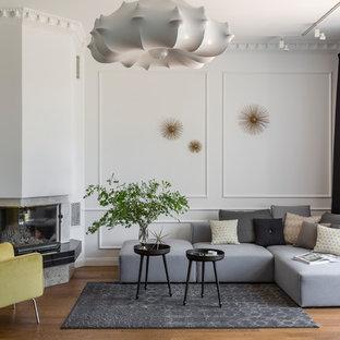 На фото: парадные гостиные комнаты среднего размера в современном стиле с угловым камином, белыми стенами, паркетным полом среднего тона и коричневым полом без ТВ