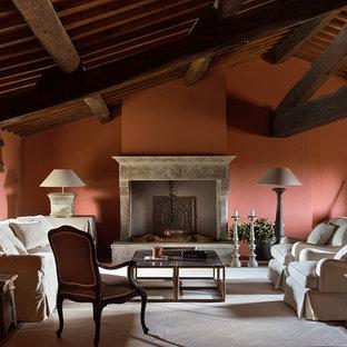 Immagine di un soggiorno classico con camino classico e pareti arancioni