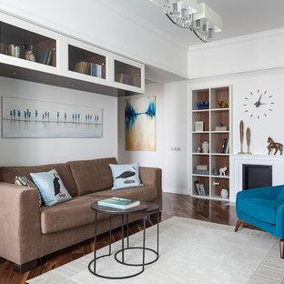 Неиссякаемый источник вдохновения для домашнего уюта: маленькая изолированная гостиная комната в стиле современная классика с библиотекой, белыми стенами, темным паркетным полом и коричневым полом