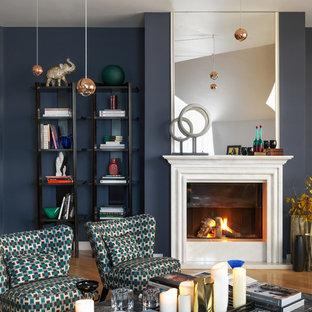 Пример оригинального дизайна: парадная гостиная комната в современном стиле с светлым паркетным полом, стандартным камином, фасадом камина из камня, синими стенами и бежевым полом
