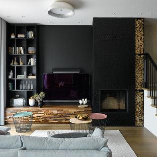 Неиссякаемый источник вдохновения для домашнего уюта: открытая гостиная комната среднего размера в современном стиле с черными стенами, паркетным полом среднего тона, стандартным камином, фасадом камина из металла, телевизором на стене и библиотекой