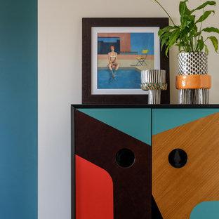 Diseño de salón con barra de bar abierto, contemporáneo, pequeño, sin televisor, con paredes verdes, suelo laminado y suelo negro